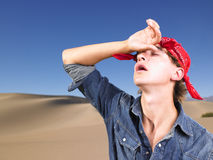 Young Man With Eyes Closed Wearing Bandana. Young man in with eyes closed wearing red bandana wiping forehead. Horizontal shot Stock Photo