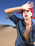 Young Man With Eyes Closed Wearing Bandana. Young man in with eyes closed wearing red bandana wiping forehead. Vertical shot Stock Photography
