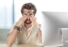 Young man with eyes pain touching his eyes. In office Stock Photos