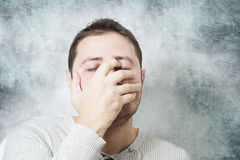 Young man with face closed by hand Stock Photo