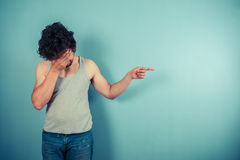 Young man with face in his palms is potining Royalty Free Stock Image