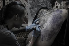 Young man with a face tattoo is getting a full back tattoo by Black Art Tattoo Studio  royalty free stock images