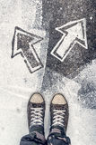Young man facing decision making situation. In life, youth generation Y male wearing worn gray sneakers standing on the street over arrows pointing to different Stock Photography