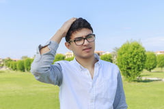 Young man facing a problem putting hand over his head. Stock Photo