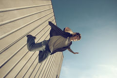 Young man is falling from a building. And calling with cell phone Stock Images