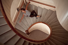 Young man falling down the steep stairs. Young man falling down into the steep spiral staircase Royalty Free Stock Image