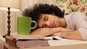 Young man falling on a sleep while studying Stock Images