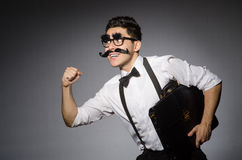 Young man with false moustache holding case Royalty Free Stock Photography