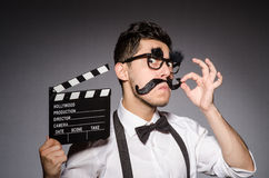 Young man with false moustache holding clapperboard Royalty Free Stock Photography