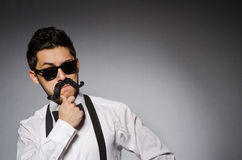 Young man with false moustache isolated on gray Stock Photo