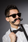 Young man with false moustache isolated on gray Royalty Free Stock Photo