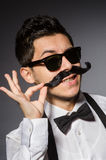 Young man with false moustache isolated on gray Royalty Free Stock Photos