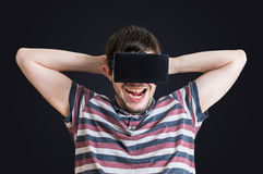Young man is fascinated from virtual reality headset. Stock Images