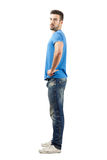 Young man fashion model standing side view Royalty Free Stock Image