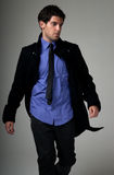 Young man fashion suit walking over grey Royalty Free Stock Photography
