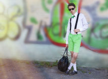 A young man in fashionable clothes with a bag standing on wall b. Ackground on a city street Royalty Free Stock Photo