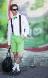A young man in fashionable clothes with a bag standing on wall b. Ackground on a city street Stock Images