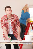 Young Man Fed Up With Decorating Home. Man Fed Up With Decorating Home Royalty Free Stock Photography