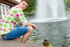 Young man feeding ducks in a pond Stock Photos