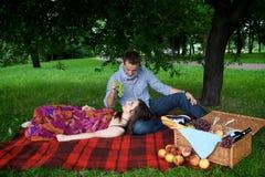 Young man feeding girlfriend Stock Photography