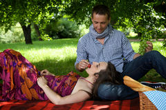 Young man feeding girlfriend at park Stock Photos
