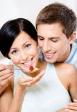 Young man feeds his girlfriend Royalty Free Stock Image
