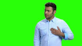 Young man feeling pain in chest. Unhappy Indian guy touching his chest on Alpha Channel background. Human expression of pain stock video