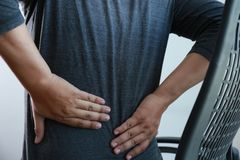 Young man Feeling suffering  Lower back pain  Pain relief concep Royalty Free Stock Photos