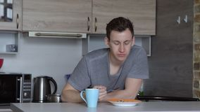 Young man, fell asleep, oat breakfast cereal in the kitchen.  stock video footage