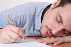 Young man Fell asleep signing contracts Royalty Free Stock Image
