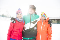 Young man with female friends standing arm around in snow Stock Image