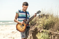 The young man on the field, the musician with the guitar and amp, the concept of music and art Stock Images