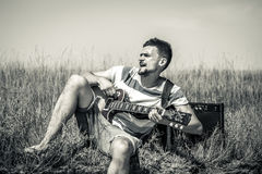 The young man on the field, the musician with the guitar and amp, the concept of music and art Stock Photo
