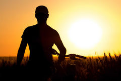 A young man in a field near a bicycle Royalty Free Stock Photo