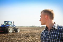 Young man in a field and a tractor on a background. Royalty Free Stock Photos