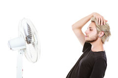 Young man fighting with wind from cooling fan Royalty Free Stock Photography