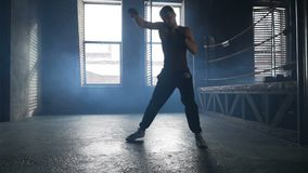 Young man fights the shadow training near boxing ring in industrial gym. With windows. Slow motion light weight kickboxer training stock footage