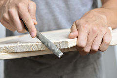 Young man filing a wooden board with a rasp Stock Photo