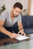 Young man filling model release on glass desk Stock Image