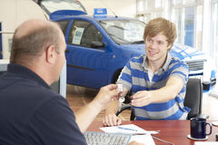 Young man filling in paperwork in car showroom Stock Image
