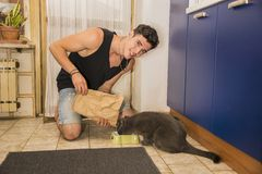 Young Man Filling Pet Bowl with Dry Food for Cat Royalty Free Stock Photography