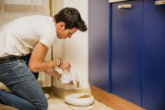 Young Man Filling Pet Bowl with Dry Food Stock Photography