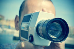 Young man filming with a retro film camera Royalty Free Stock Image