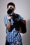 Young man filmmaker with old movie camera and a suitcase in his. Hand Royalty Free Stock Image