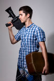 Young man filmmaker with old movie camera and a suitcase in his Royalty Free Stock Image