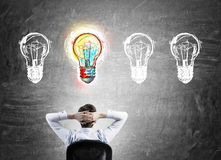 Young man finding inspiration. Businessman sitting with back to viewer and looking at four light bulbs on blackboard. Concept of inspiration Stock Photos