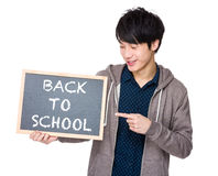 Young man finger point to chalkboard with back to scholl phrase Stock Photos