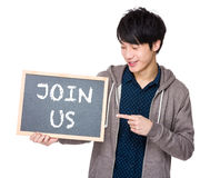 Young man finger point to chalkboard showing a phrase of join us Royalty Free Stock Images