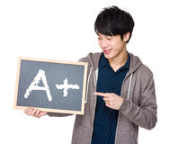 Young man finger point to chalkboard showing sign of A plus. Isolated on white background Royalty Free Stock Image