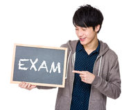 Young man finger point to chalkboard showing a word exam Royalty Free Stock Image